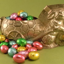 Foil wrapped chocolate eggs, pictured in an antique chocolate bunny mold