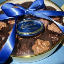 round gold gift box of gourmet chocolate clusters
