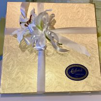 gold box of gourmet chocolates decorated with white lilies for Mothers day